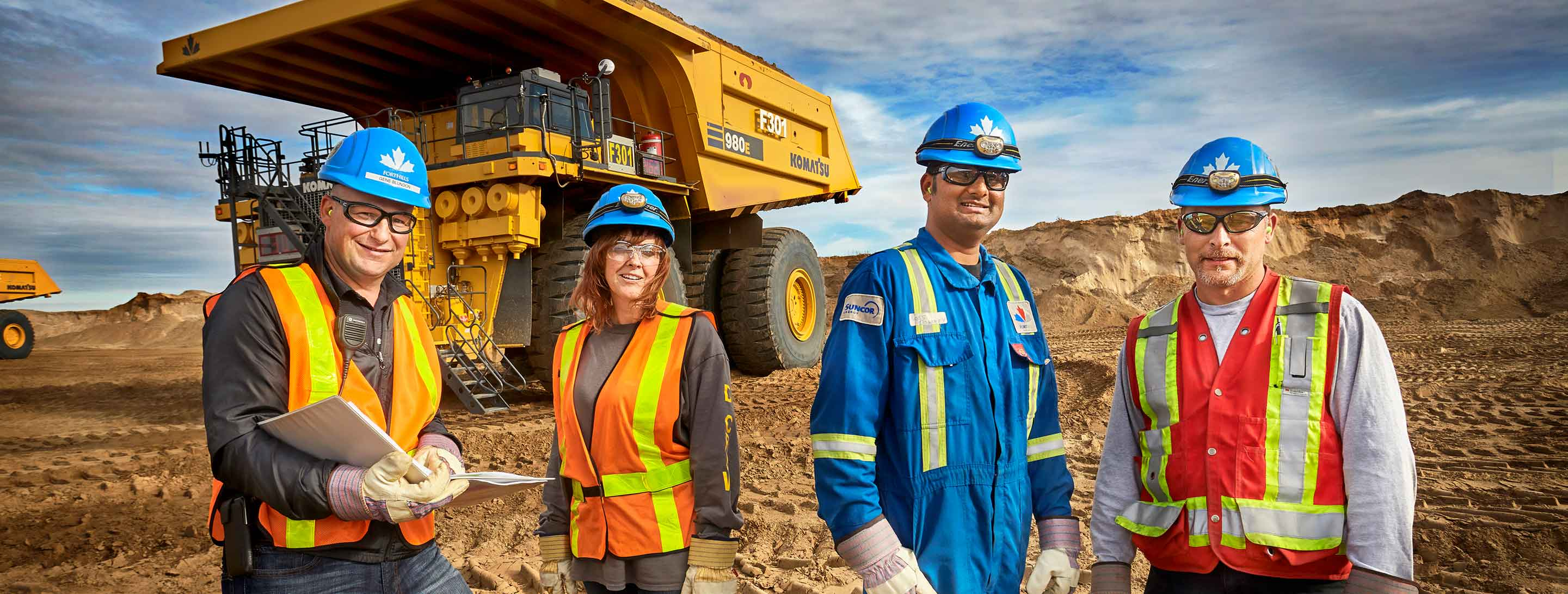 Four Fort Hills employees stand in front of a mining haul truck at the Fort Hills site, near Fort McMurray, Alberta