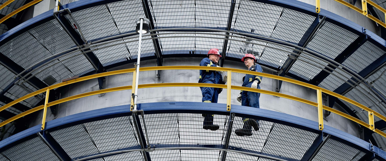 Deux travailleurs sur une voie piétonne à la raffinerie Suncor d'Edmonton, en Alberta.