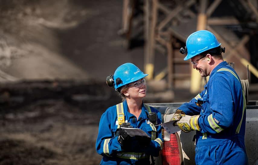 Deux travailleurs discutent à l'extérieur de l'usine de base