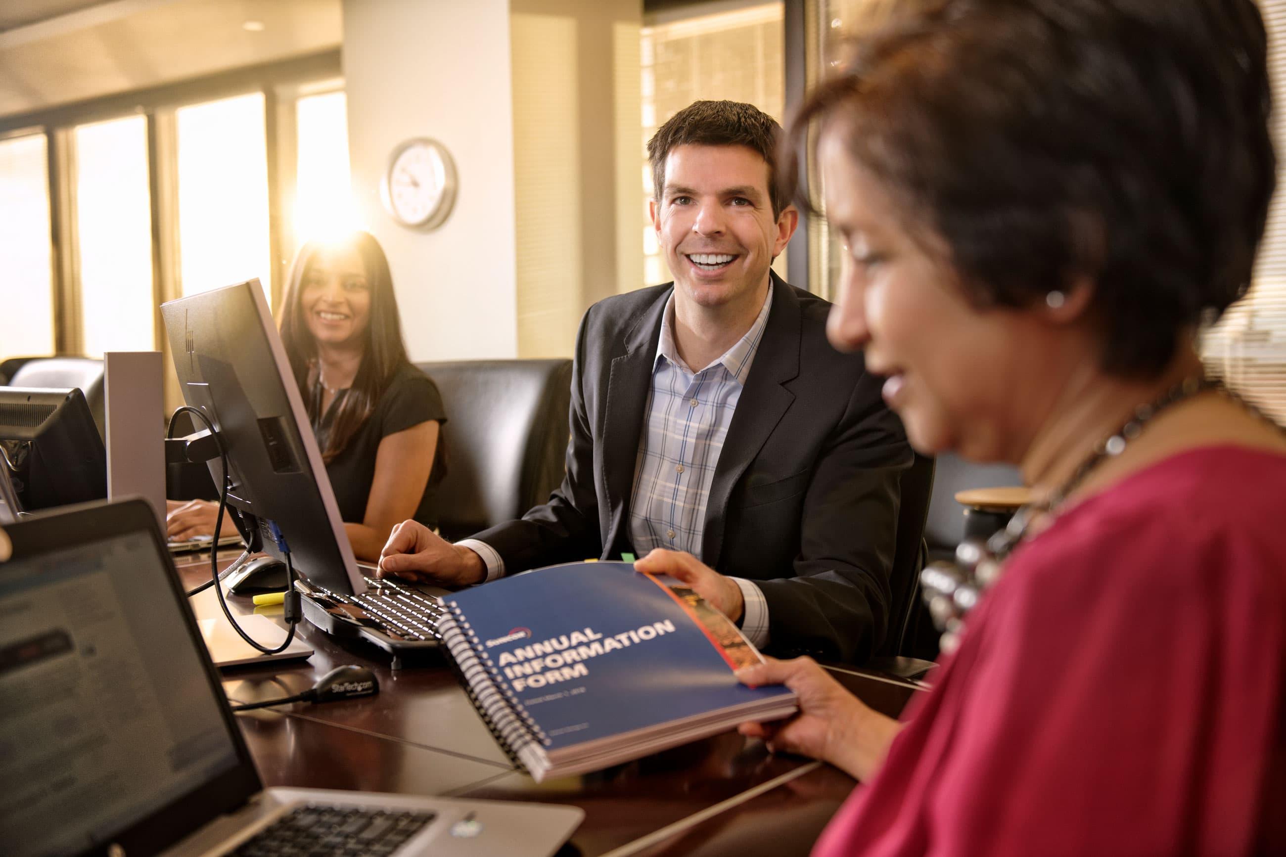 Trois employés dans la salle de réunion de la haute direction
