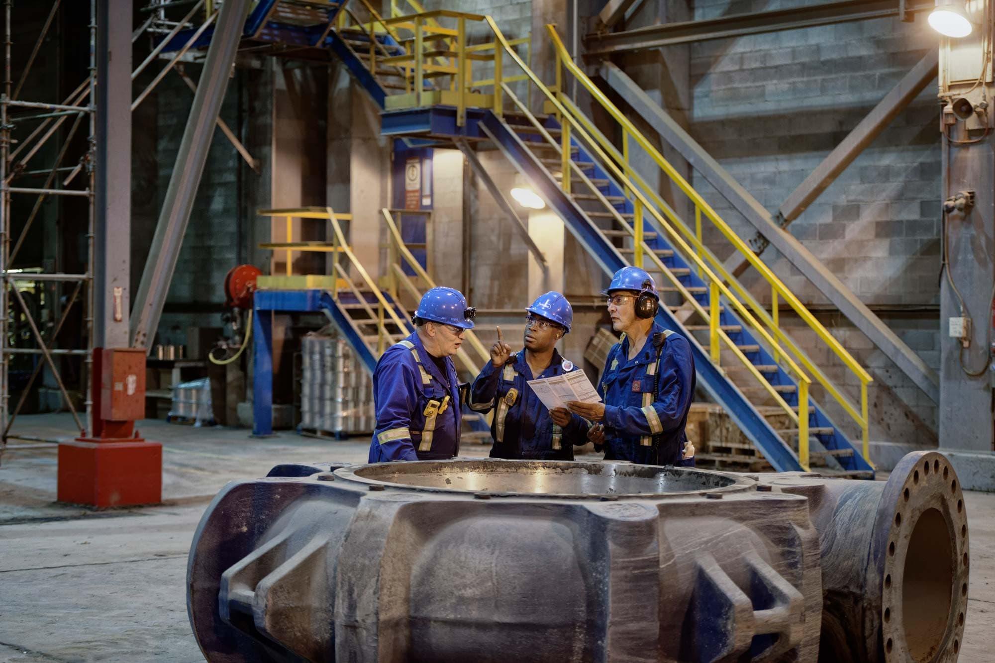 Trois travailleurs à l'intérieur de l'usine de base effectuant une évaluation des risques sur le terrain