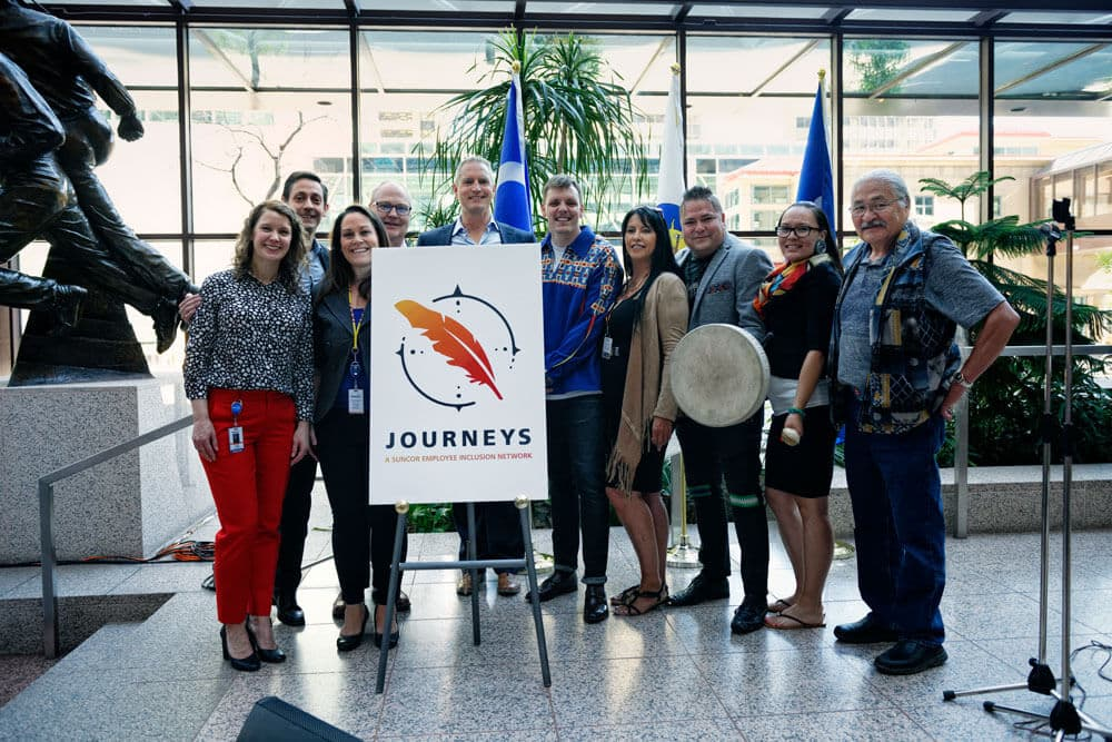 People gathered together in front of the new Journeys logo.