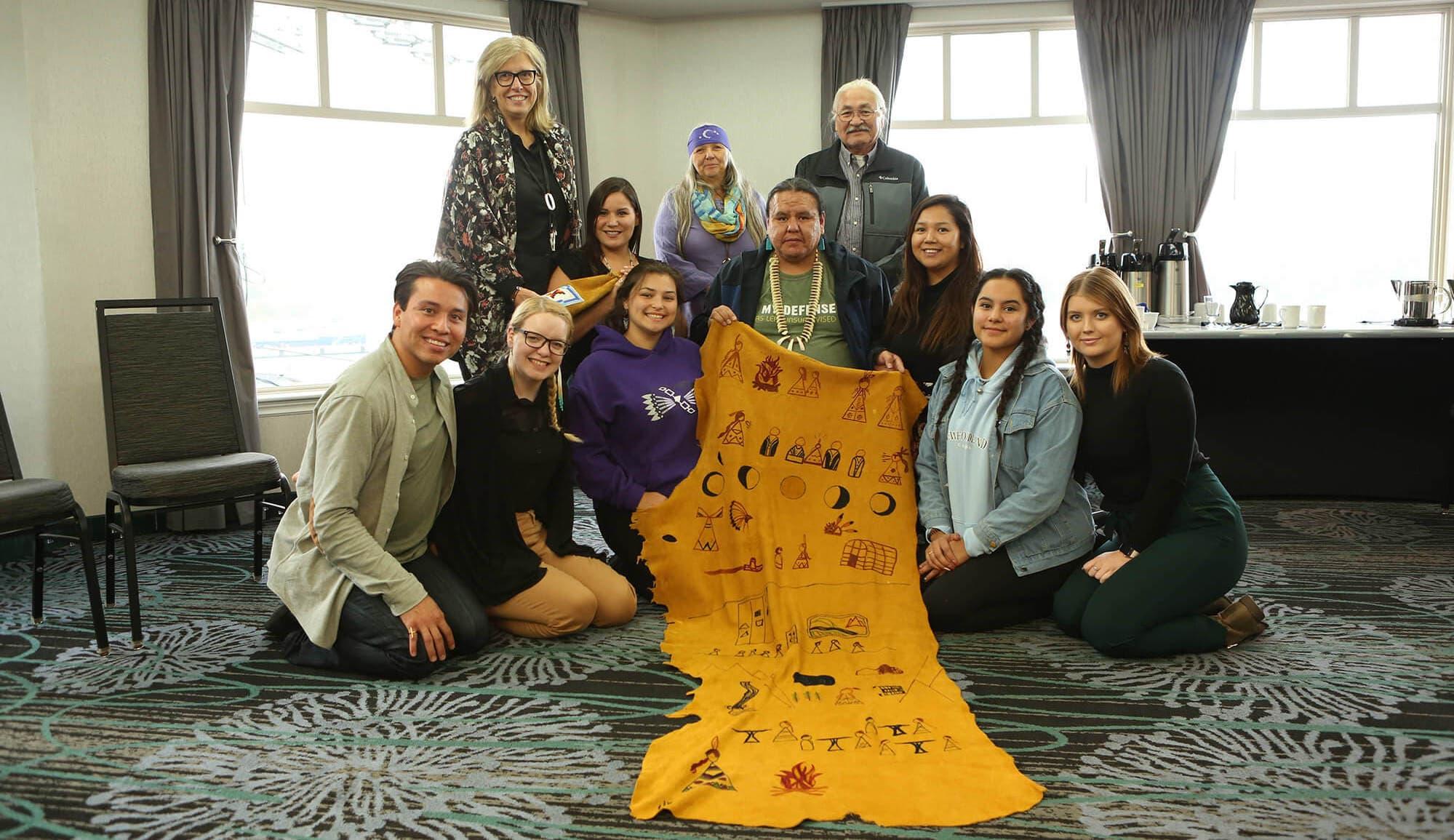 Des membres de notre Indigenous Youth Advisory Council posent avec une peau d'orignal à St. John's, Terre-Neuve-et-Labrador.