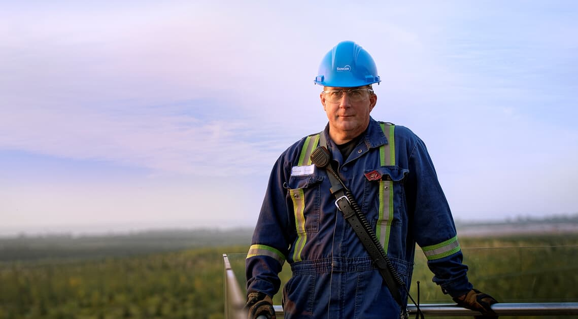 Male worker standing in front of Wapisiw Lookout at Suncor's Base Plant.