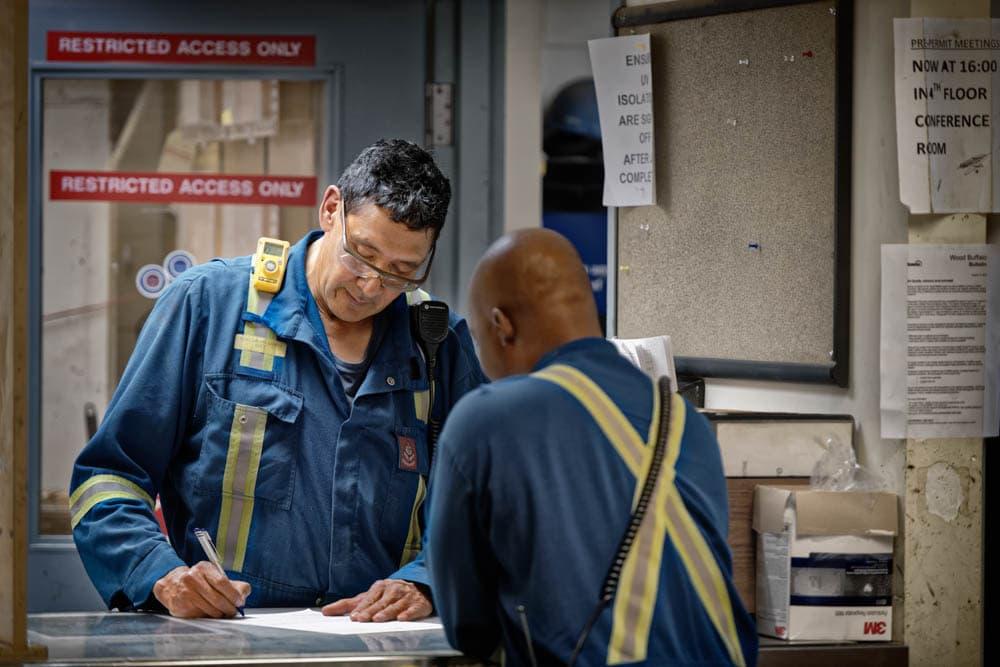Deux travailleurs au bureau des permis à l'usine d'extraction 86