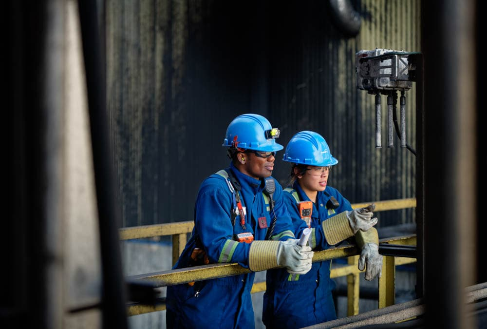 Two workers in full personal protective equipment standing at Suncor's Base Plant