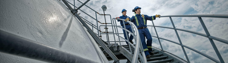 Deux travailleurs descendent un escalier.