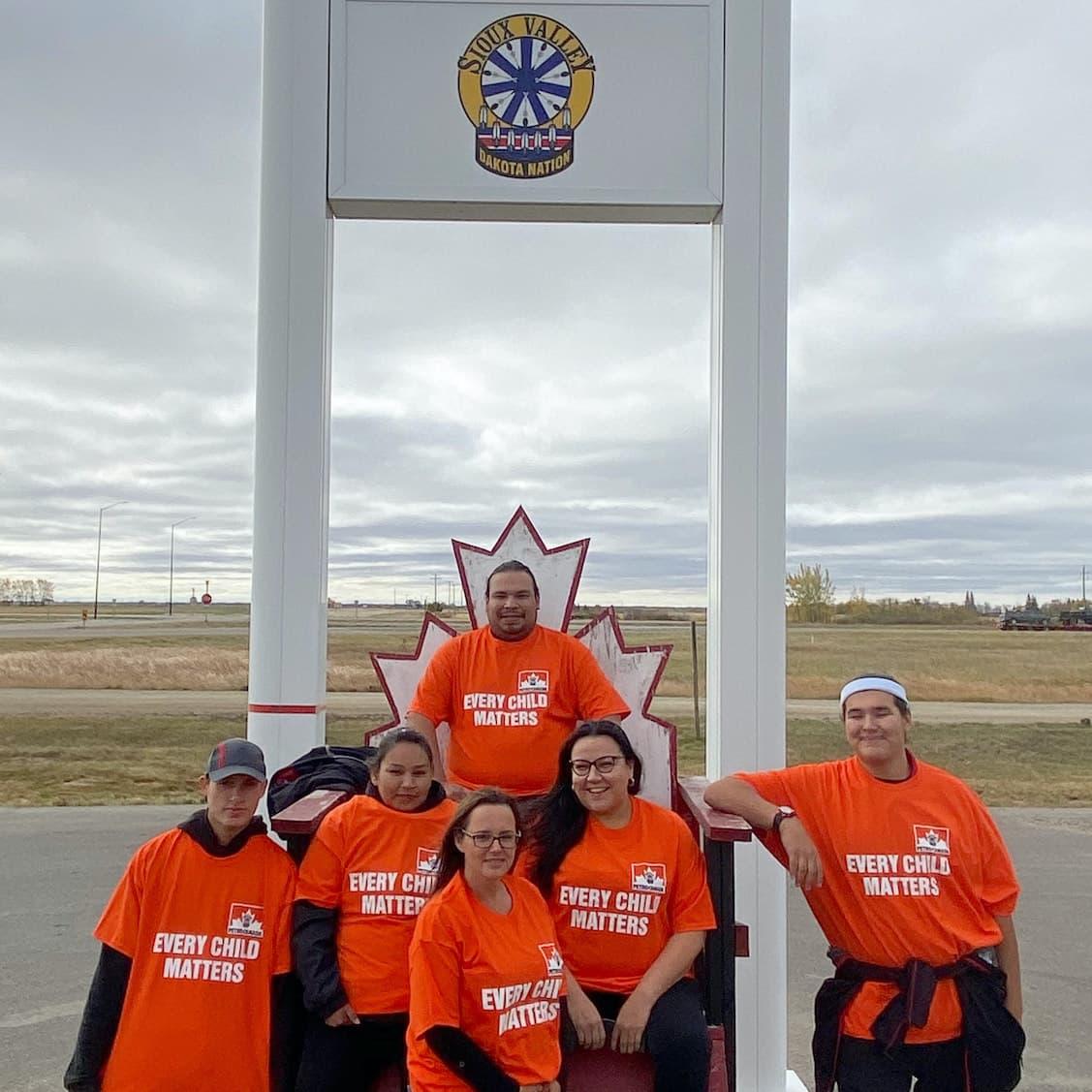 Six membres de la nation dakota de Sioux Valley posent devant une pancarte de Petro-Canada portant des chemises oranges portant l'inscription « Chaque enfant compte ».