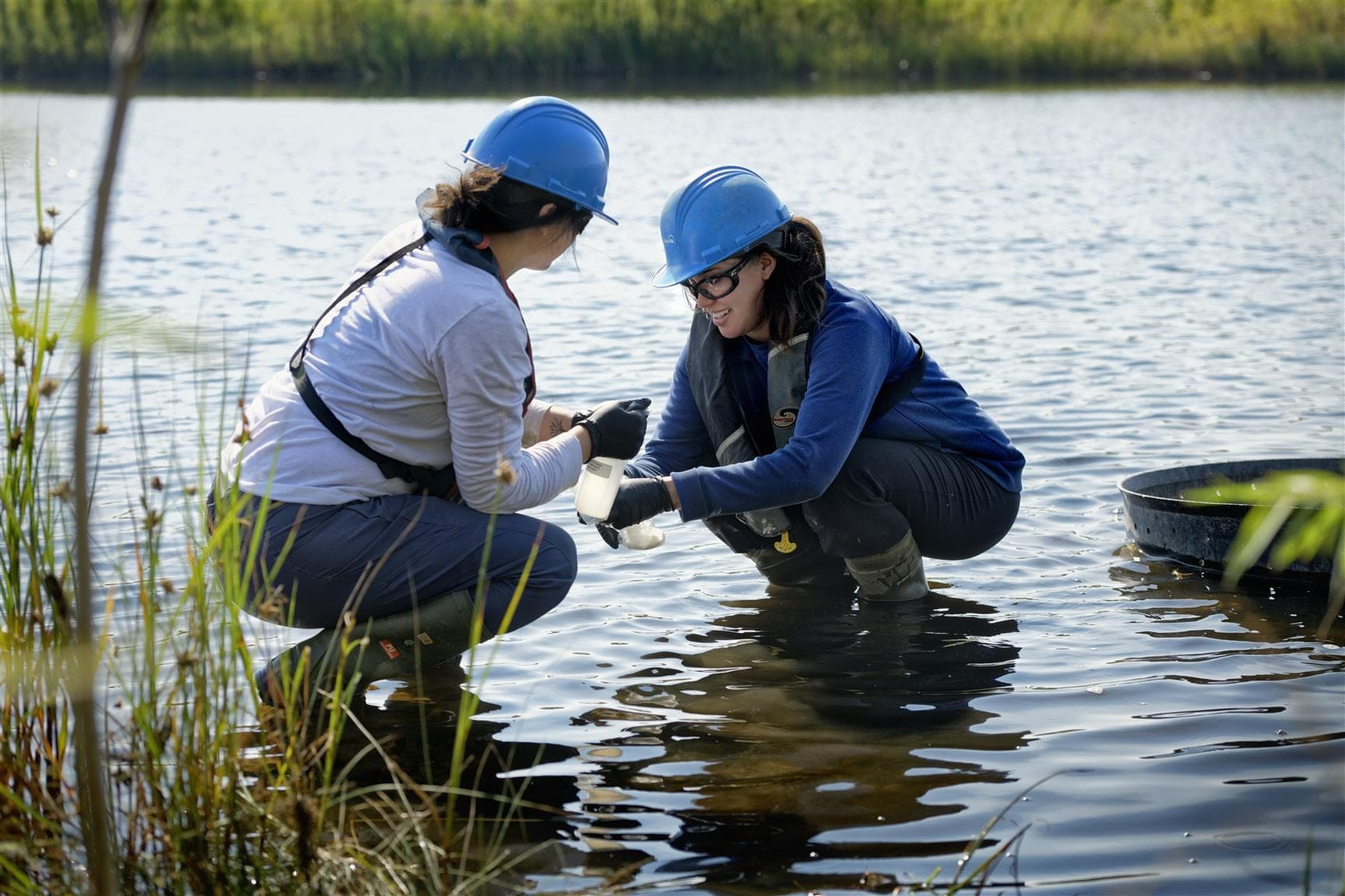 Two women in hard hats crouching in a pond while testing the water