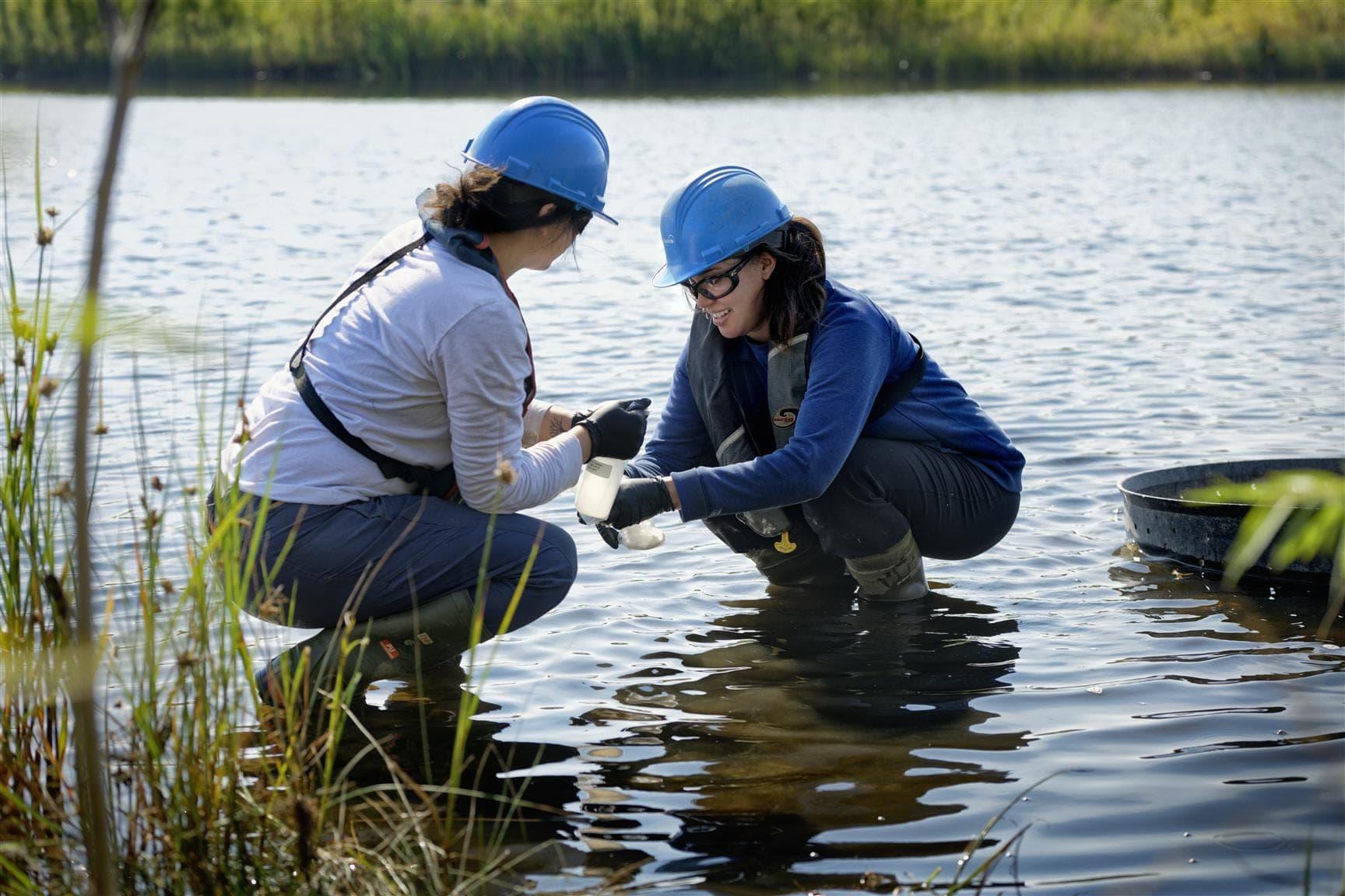 deux femmes portant des casques accroupis dans un étang tout en testant l'eau