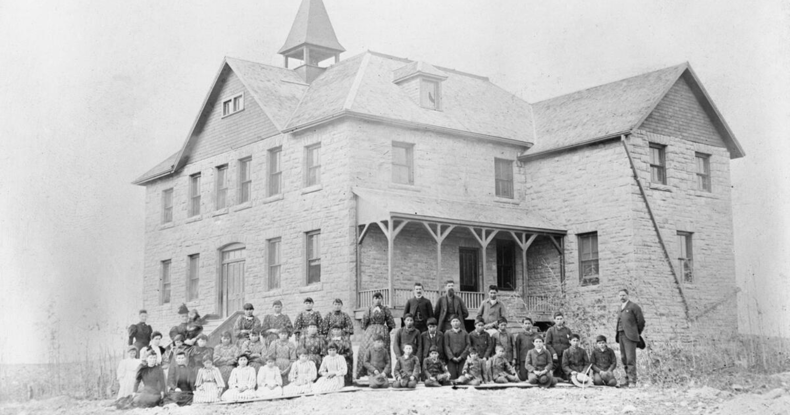 Vintage black and white picture of a institutional building with students and staff posed in front of building.