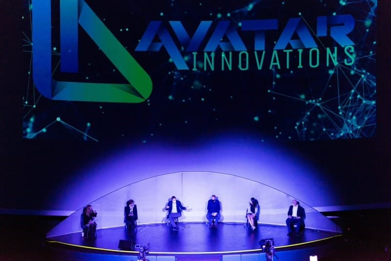 stage with avatar innovations logo and panel individuals sitting on stage