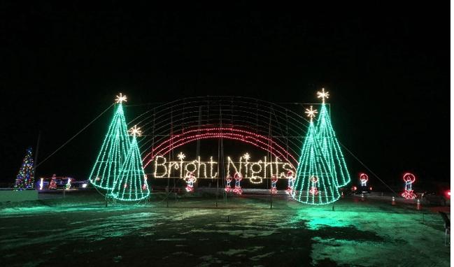 Ciel sombre avec des lumières de Noël lumineuses affichant quatre arbres de Noël et les mots nuits lumineuses