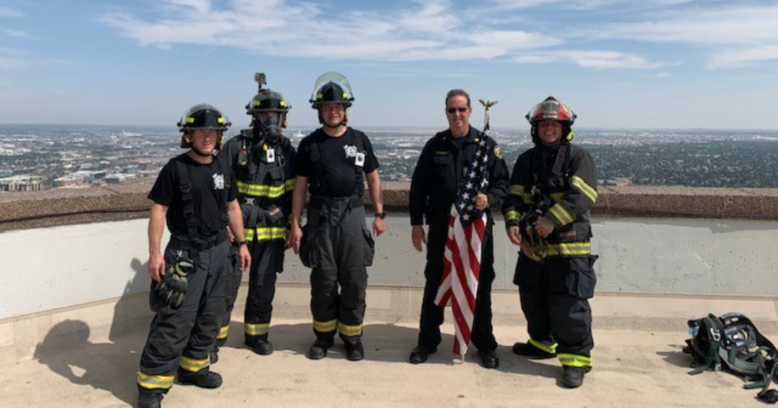 commerce city firefighters in full gear standing on top of building after completing the memorial stair climb