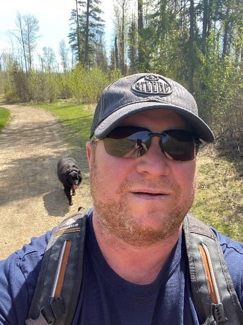 Jason Sinclair marchant à l'extérieur avec un chien noir qui le suit