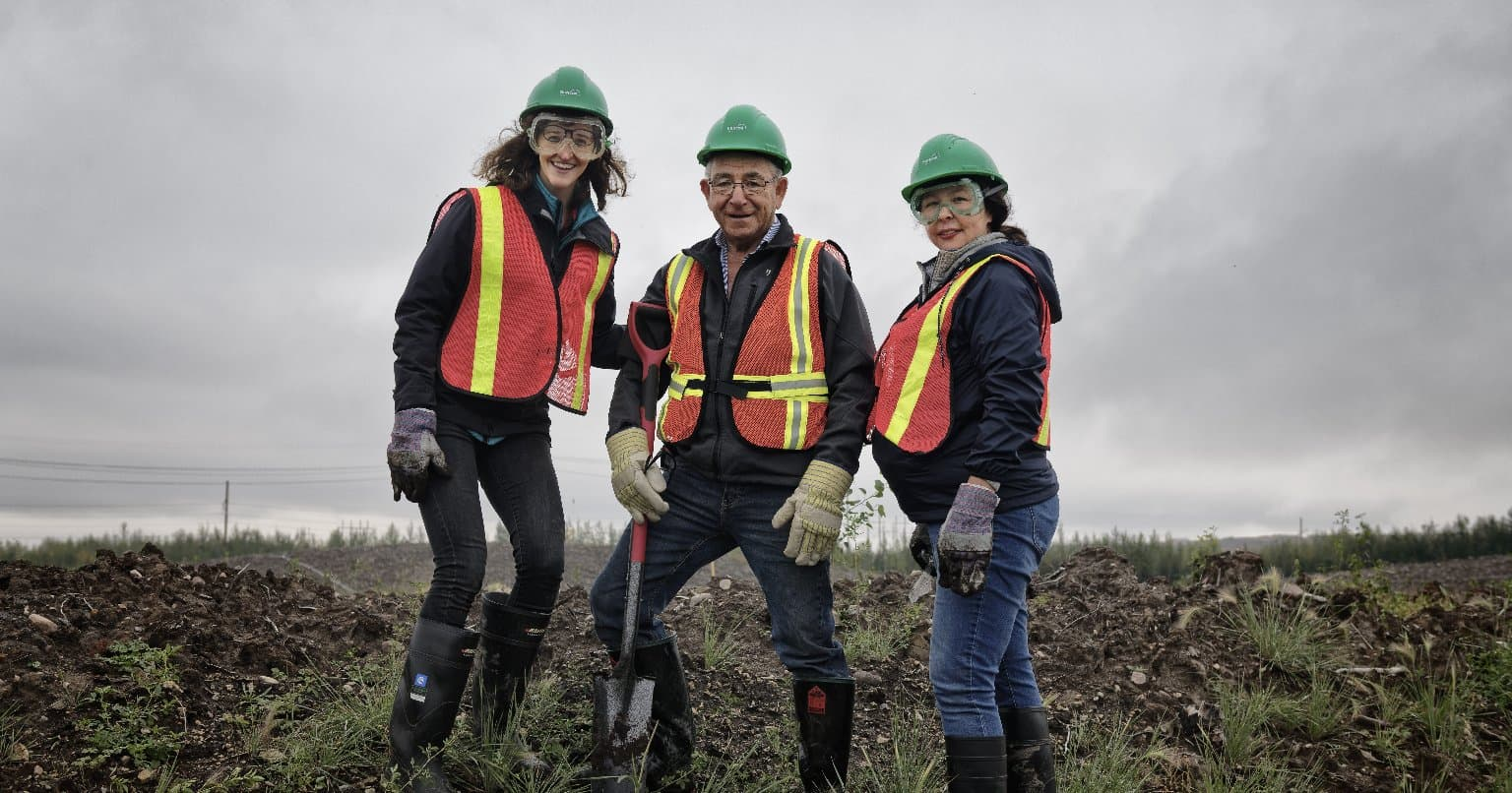 Three Suncor workers wearing personal protective equipment standing in a field