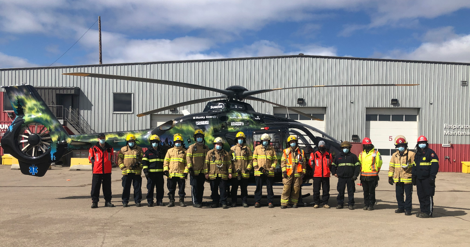 team standing in front of helicopter