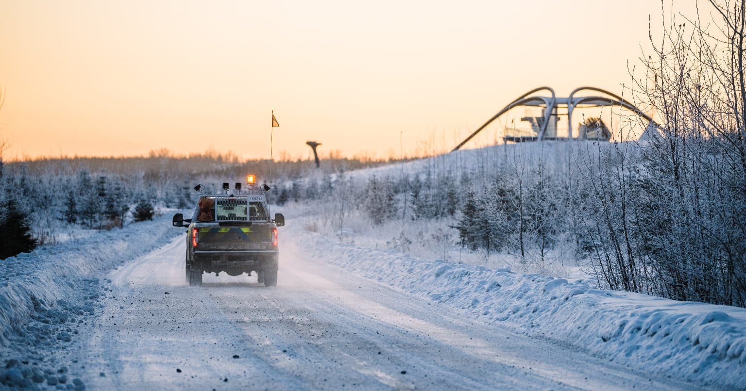 Car driving in snow with yellow sky