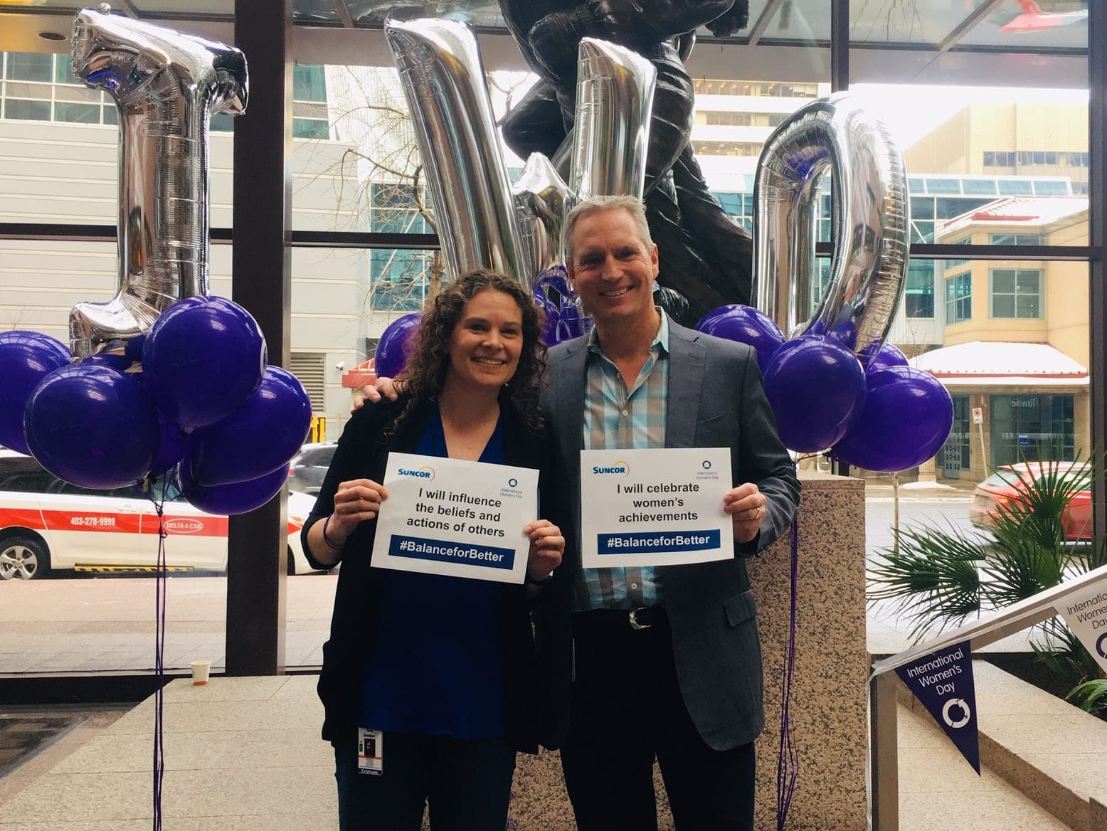 Suncor employee, Meredith McKay, and CEO Mark Little standing together in the Suncor lobby in Calgary, Alberta.