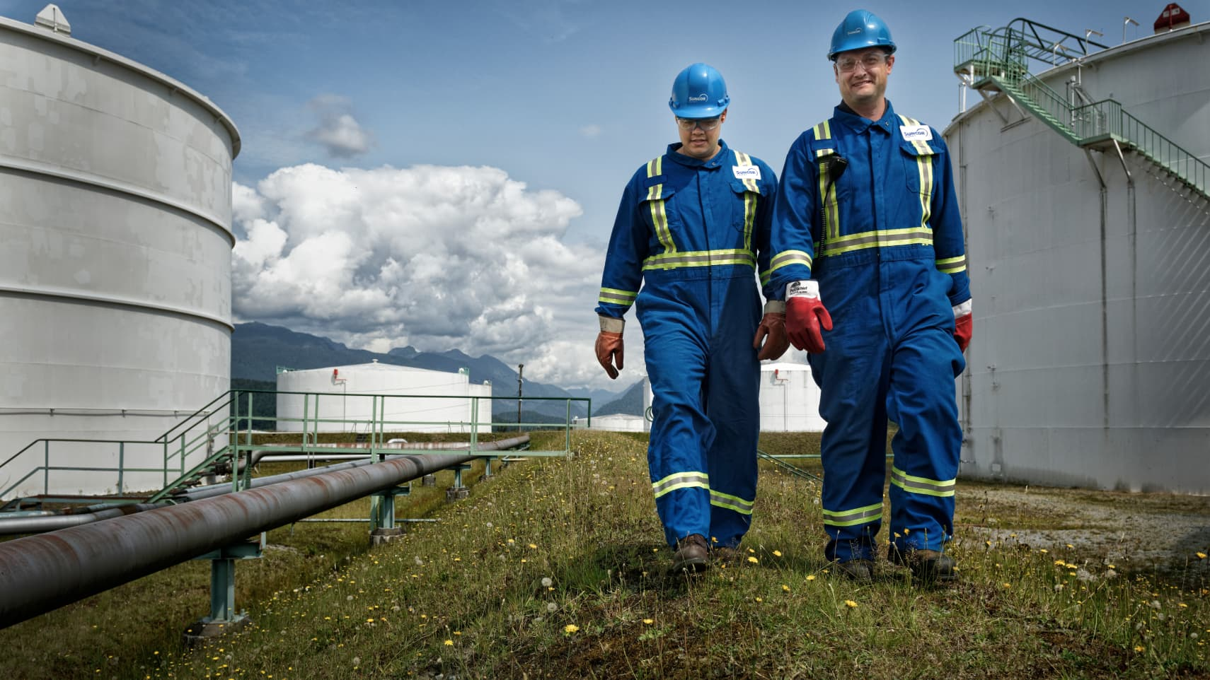man and woman walking side by side in Suncor protective equipment between tanks