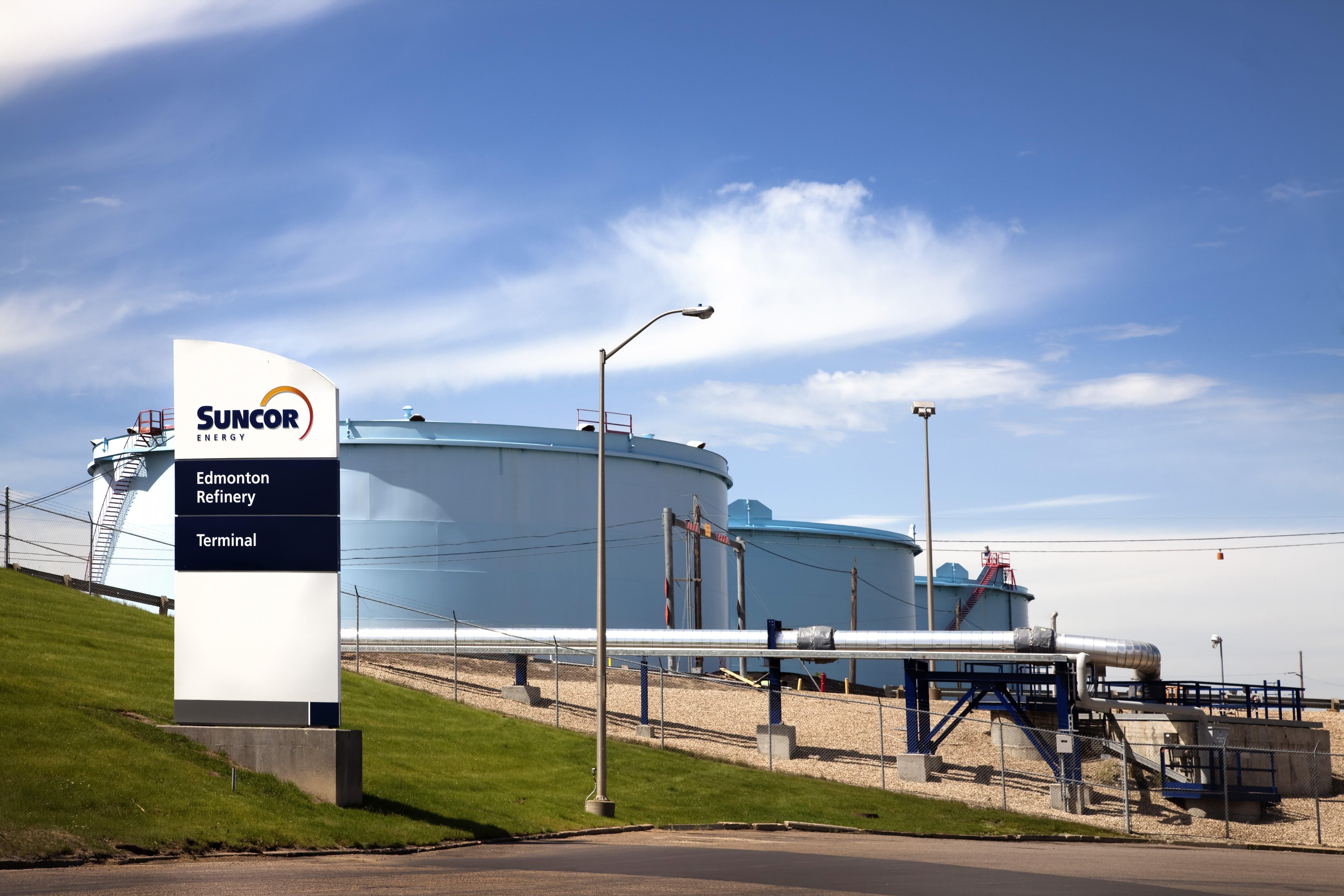 L'image a un fond de ciel bleu et la raffinerie d'Edmonton avec quatre réservoirs d'hydrogène et un panneau Suncor devant
