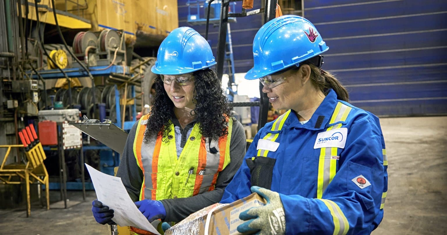 Two women in personal protective gear at our refinery