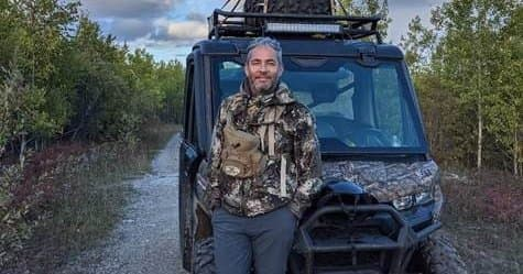 JP Gladu en tenue de camouflage debout devant un buggie de camouflage
