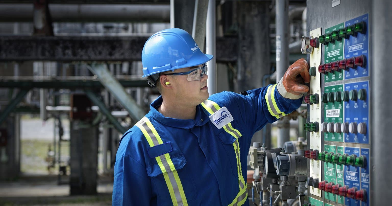 Suncor essential worker operating a plant
