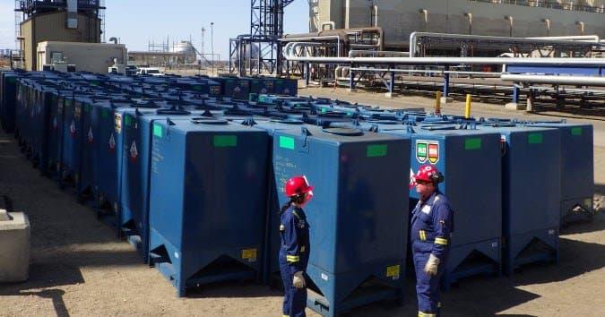 Deux travailleurs debout à l'extérieur de la raffinerie d'Edmonton