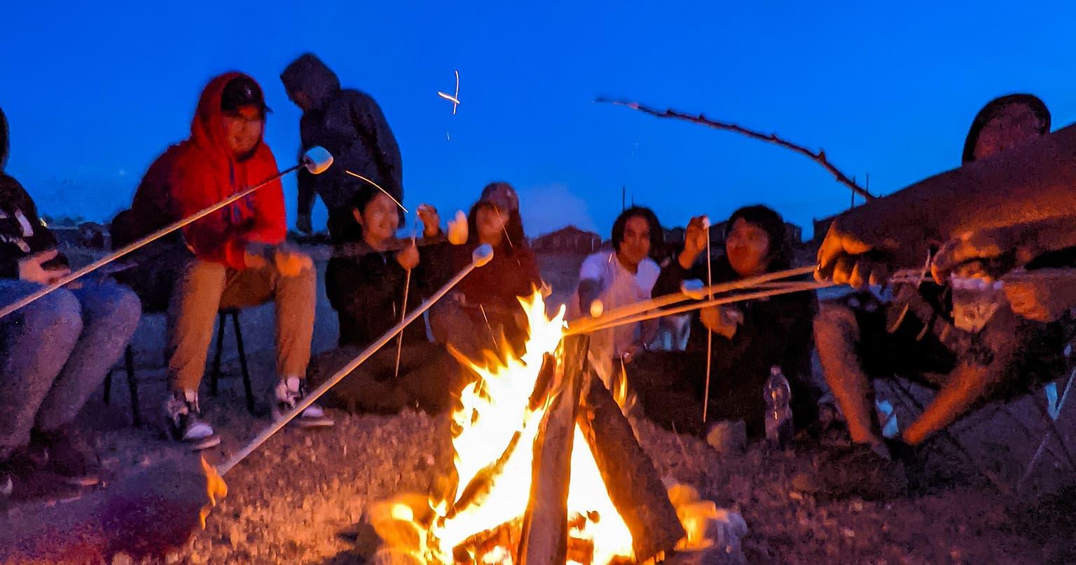 Des étudiants de la communauté crie de Waswanipi rôtissent des guimauves autour d'un feu de camp dans le cadre d'un des programmes de Fusion Jeunesse.