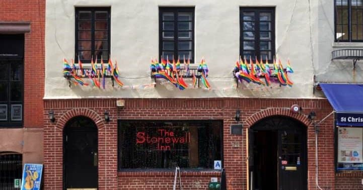 brick building with rainbow pride flags hanging out all of the windows