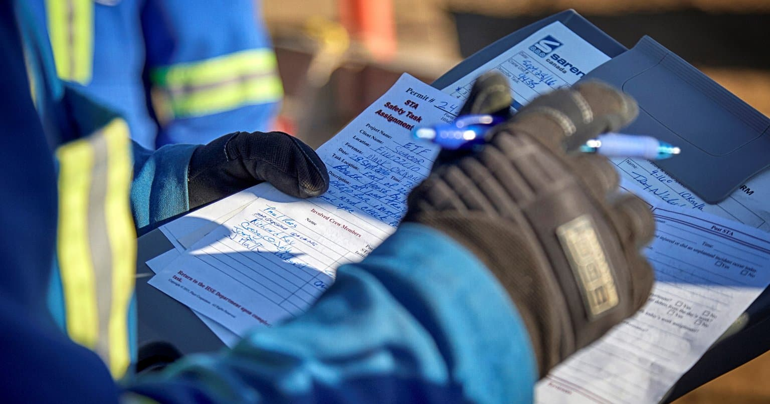 Person in blue personal protective equipment holding paperwork