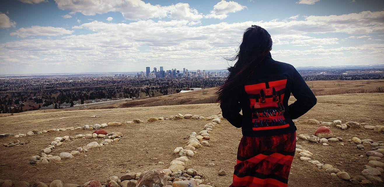 Debbie Green devant la roue médicinale des Pieds-Noirs à Nose Hill à Calgary. Debbie fait la promotion de la sensibilisation à la cause des femmes et filles autochtones disparues et assassinées (FFADA) en mémoire de sa sœur décédée alors qu'elle n'avait que 23 ans.