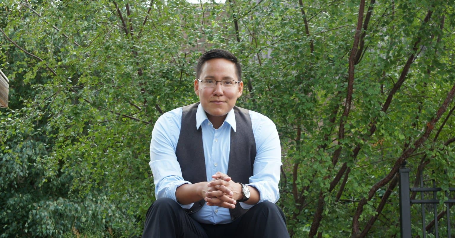 In the photo, a smiling Indigenous man sitting on stone steps wearing a button down shirt with his hands clasped on his knees.