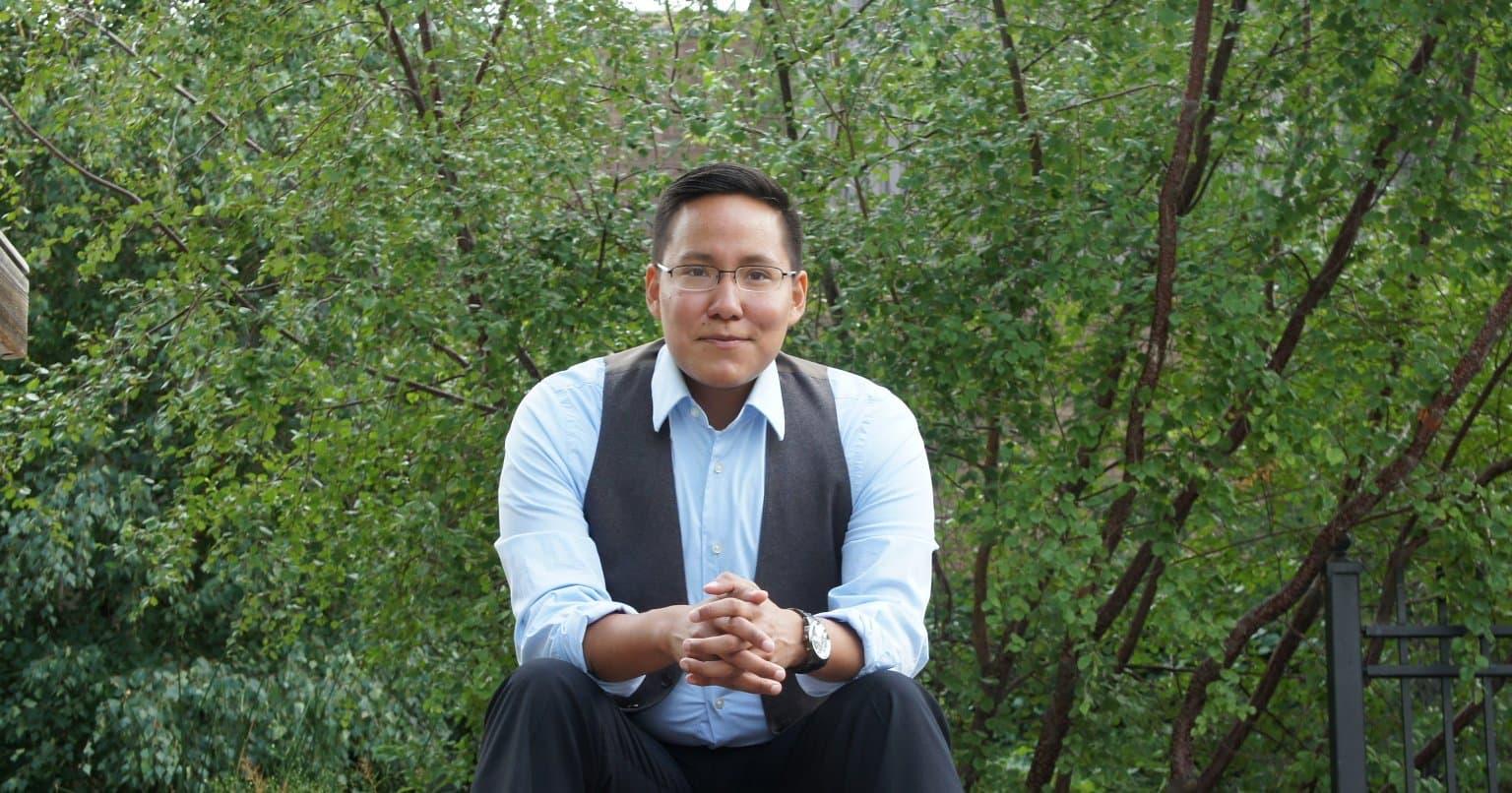 Sur la photo, un Autochtone souriant assis sur des marches de pierre portant une chemise boutonnée, les mains jointes sur les genoux.