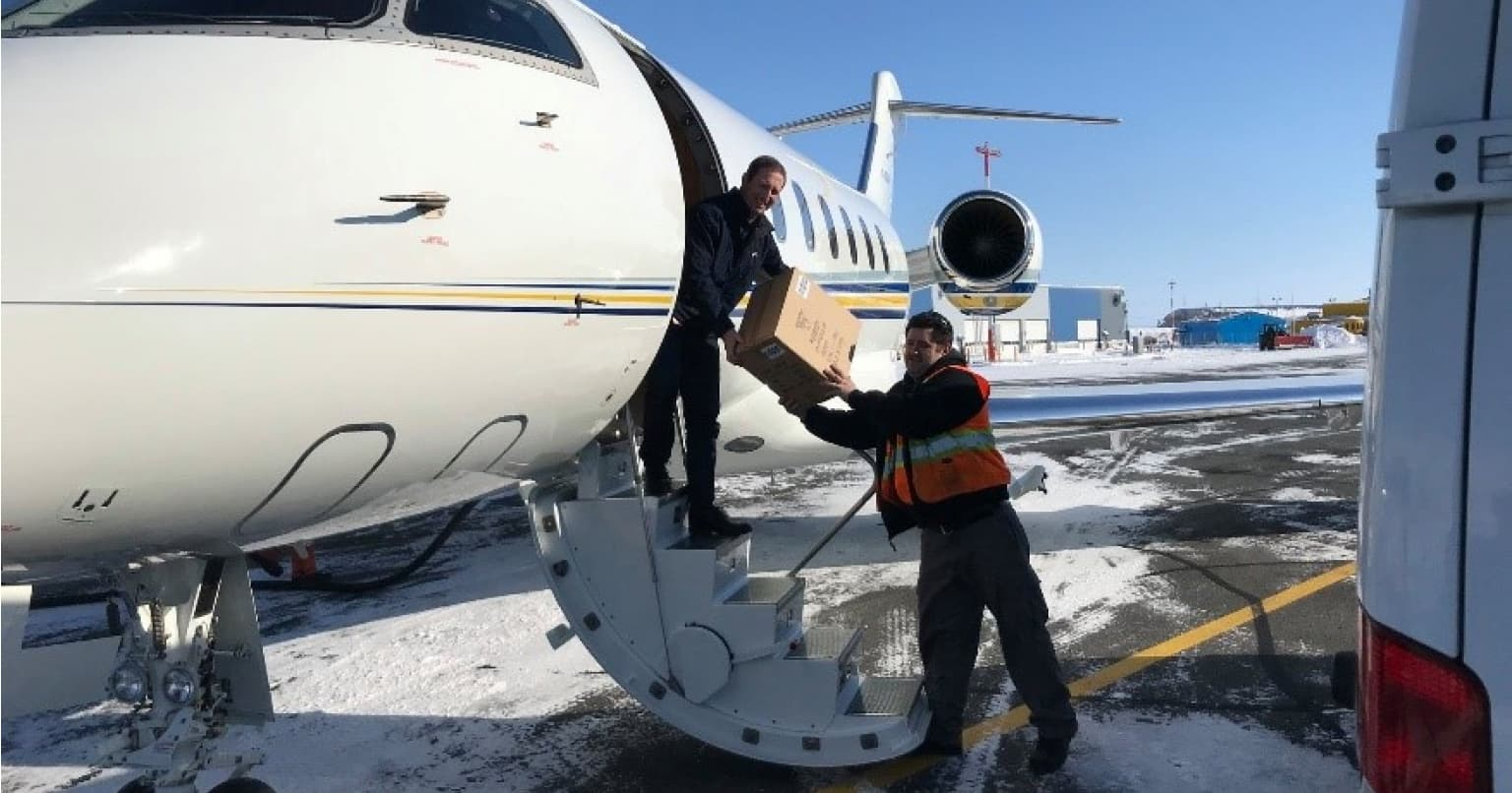 Suncor staff loading masks onto plane