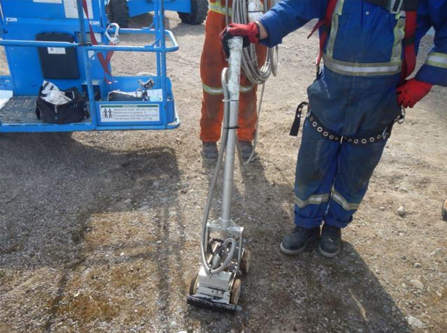 travailleur en équipement de protection individuelle complet tenant la poignée du robot rimouski debout dans un chemin de terre