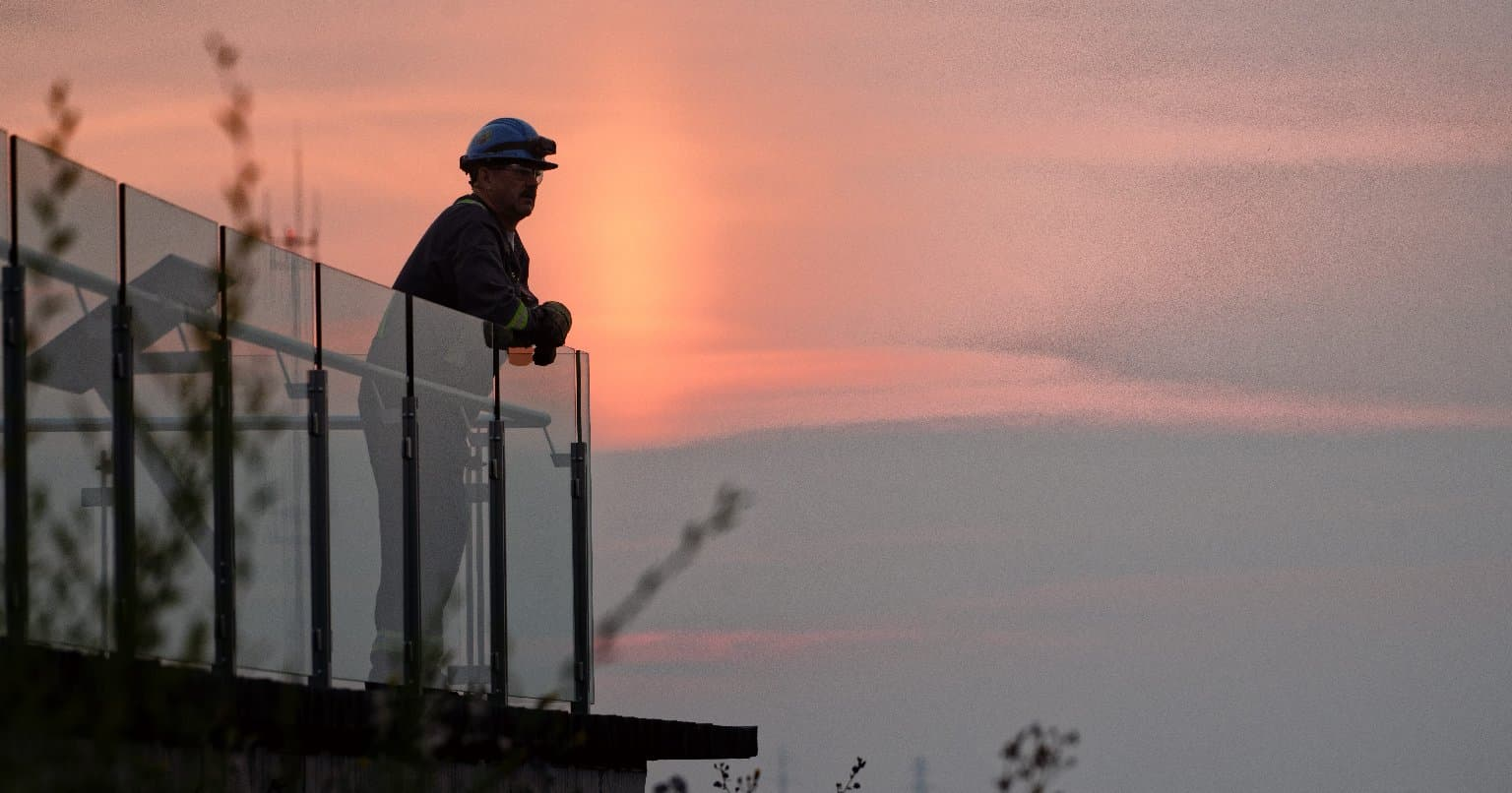 Image du lever du soleil à l'usine de base de Suncor avec l'homme dans l'ombre