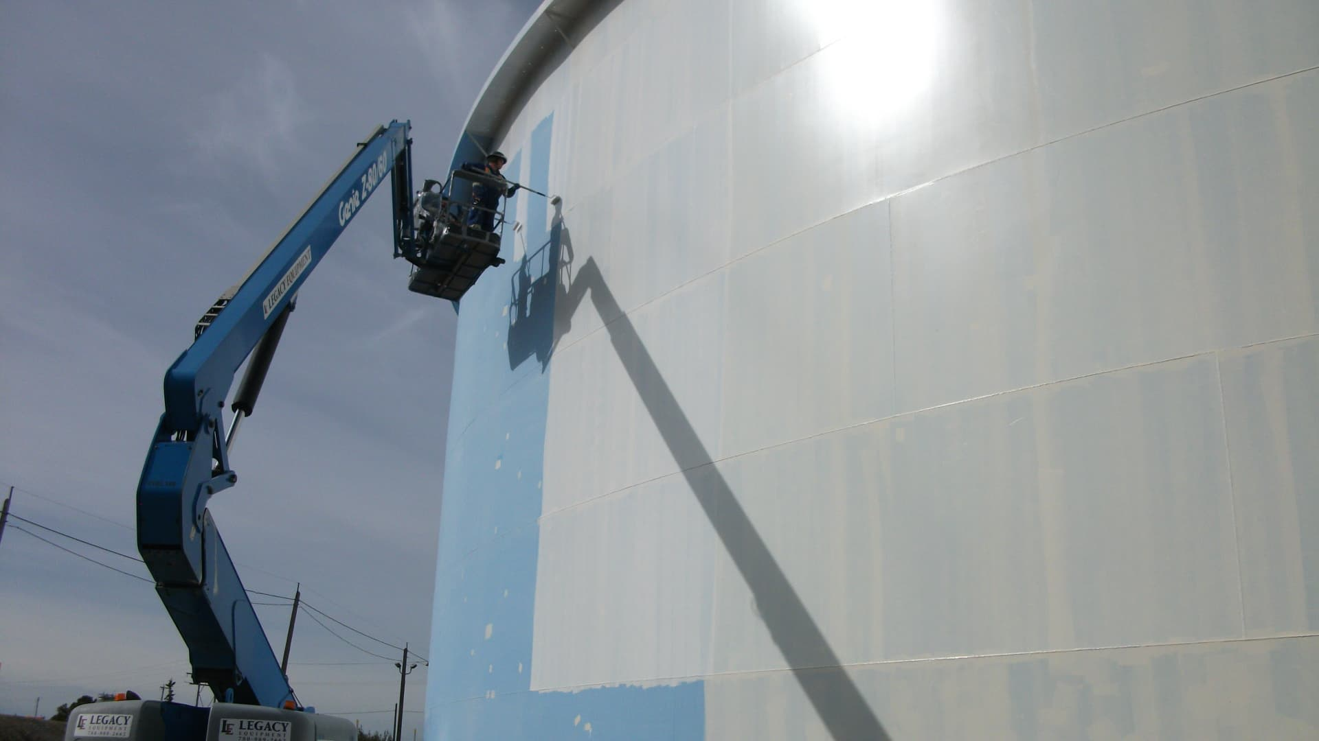 Man painting a white storage tank