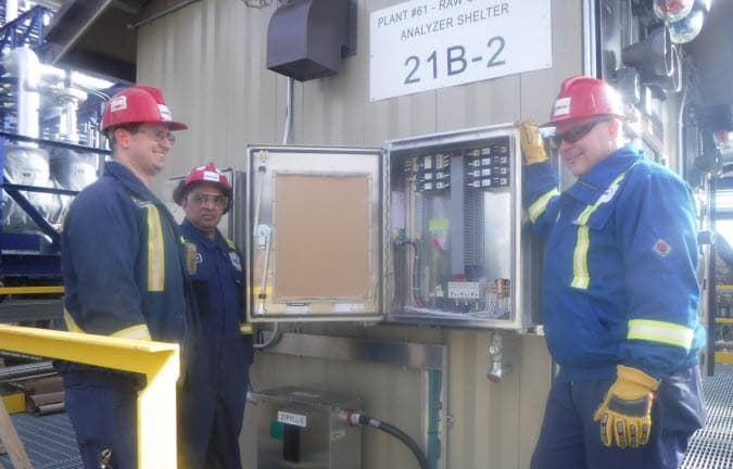 three workers standing beside control panel