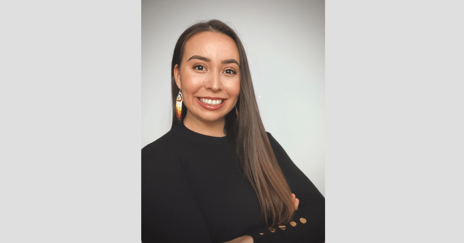 A portrait of a young Indigenous woman. The woman is wearing a black sweater and beaded earrings. She is smiling brightly with her arms crossed.