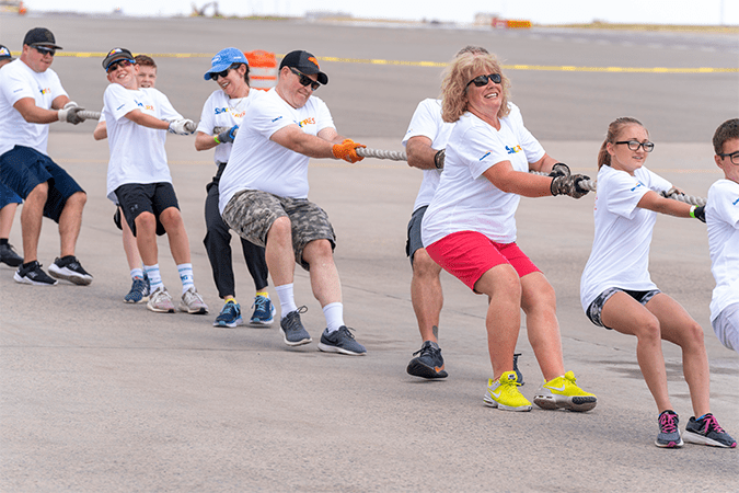 """Suncor employees and family members """"pulled for a purpose"""" this summer, hauling a 300-ton jumbo jet 12 feet in just under 11 seconds to raise money for Special Olympics Colorado."""