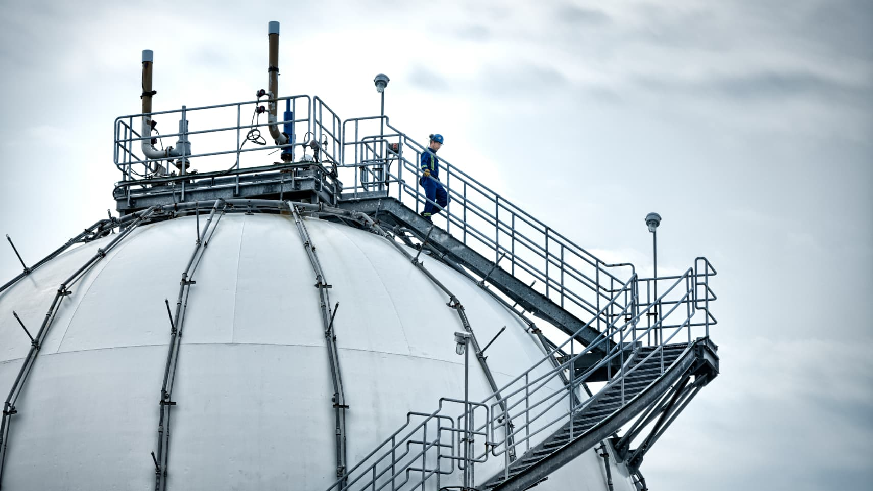 man standing on top of a refinery stepping on the metallic stairs going down