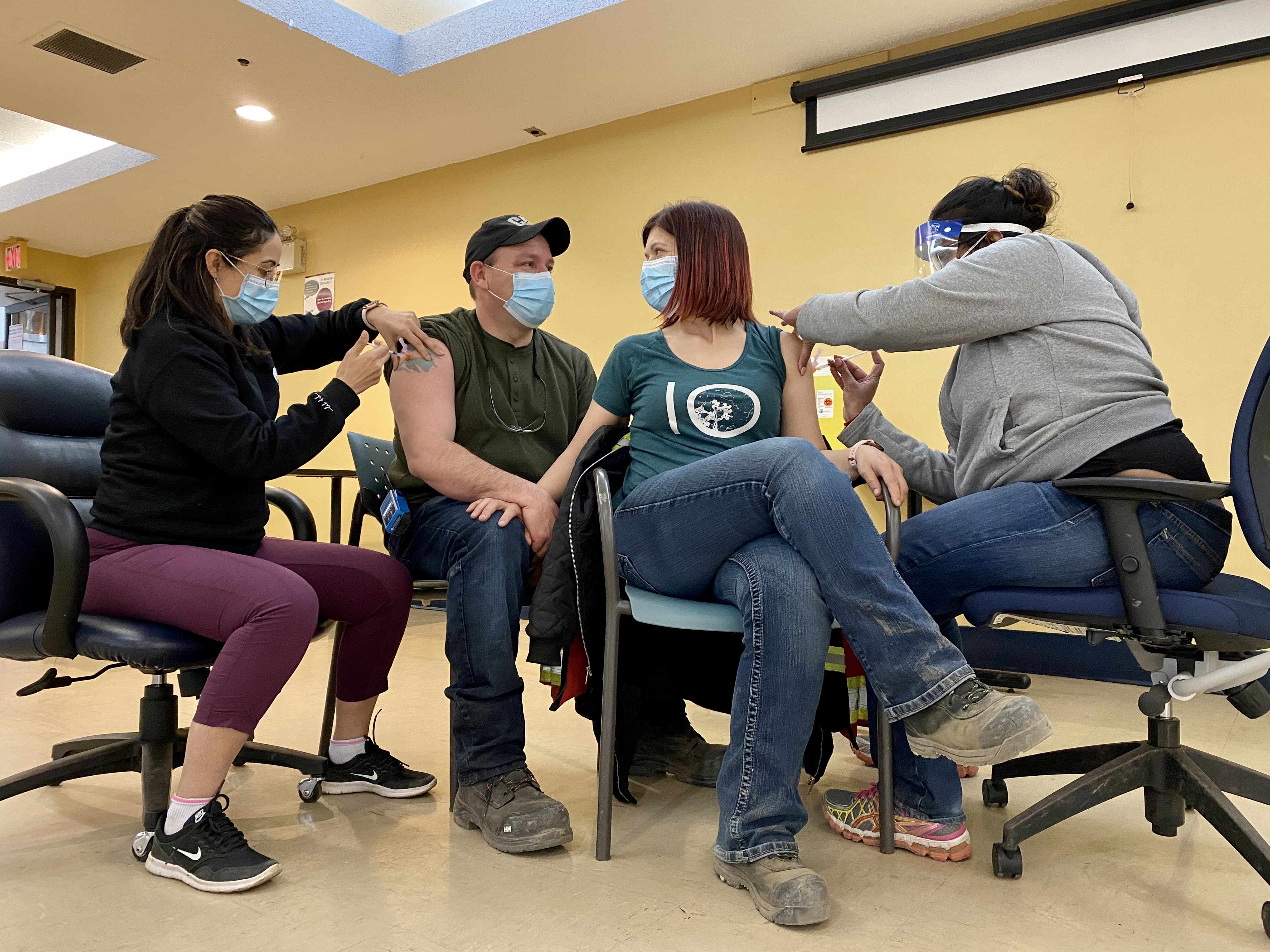 two masked people holding hands seated while they both get vaccinated by nurses
