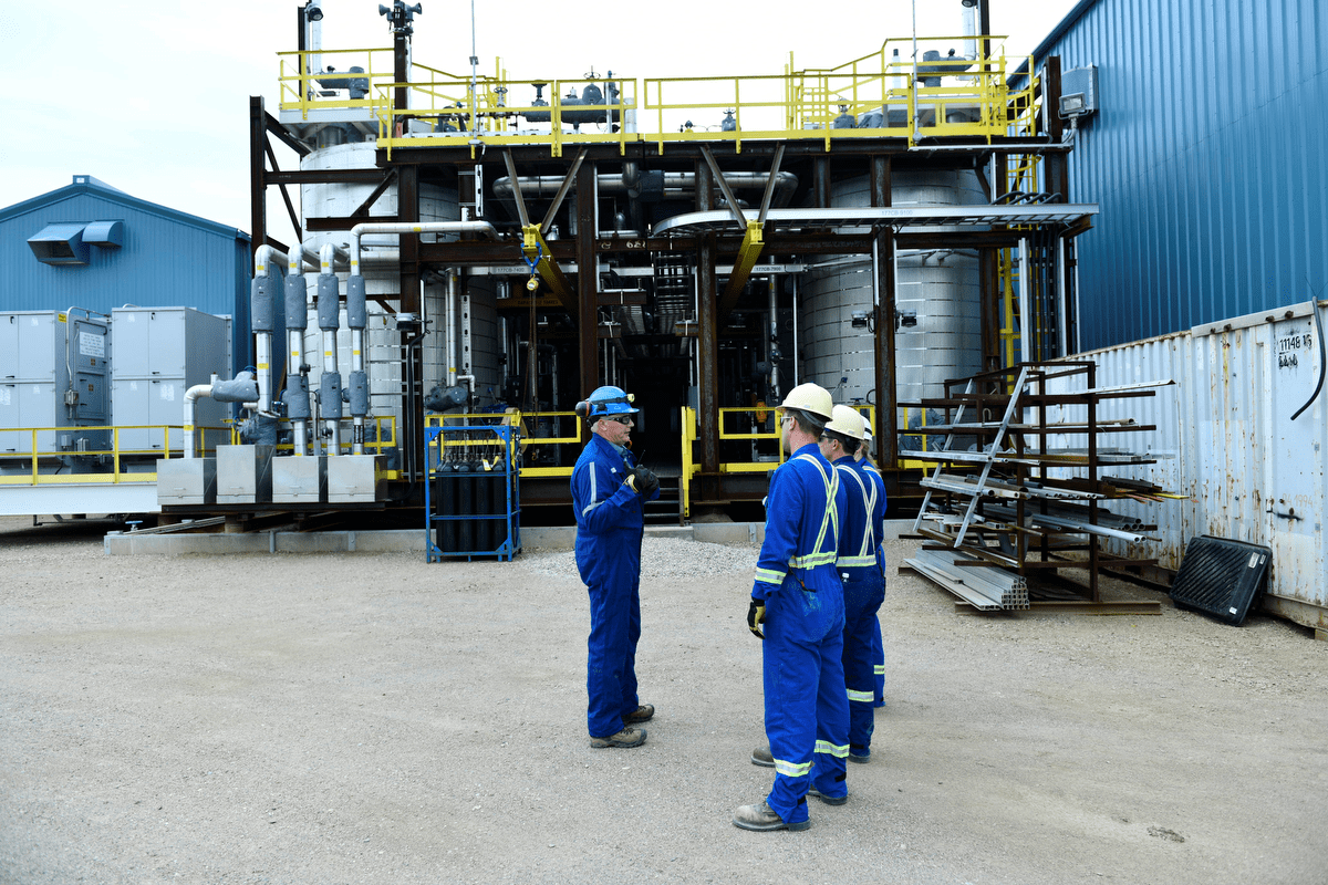 three individuals in personal protective equipment standing outside a blue facility